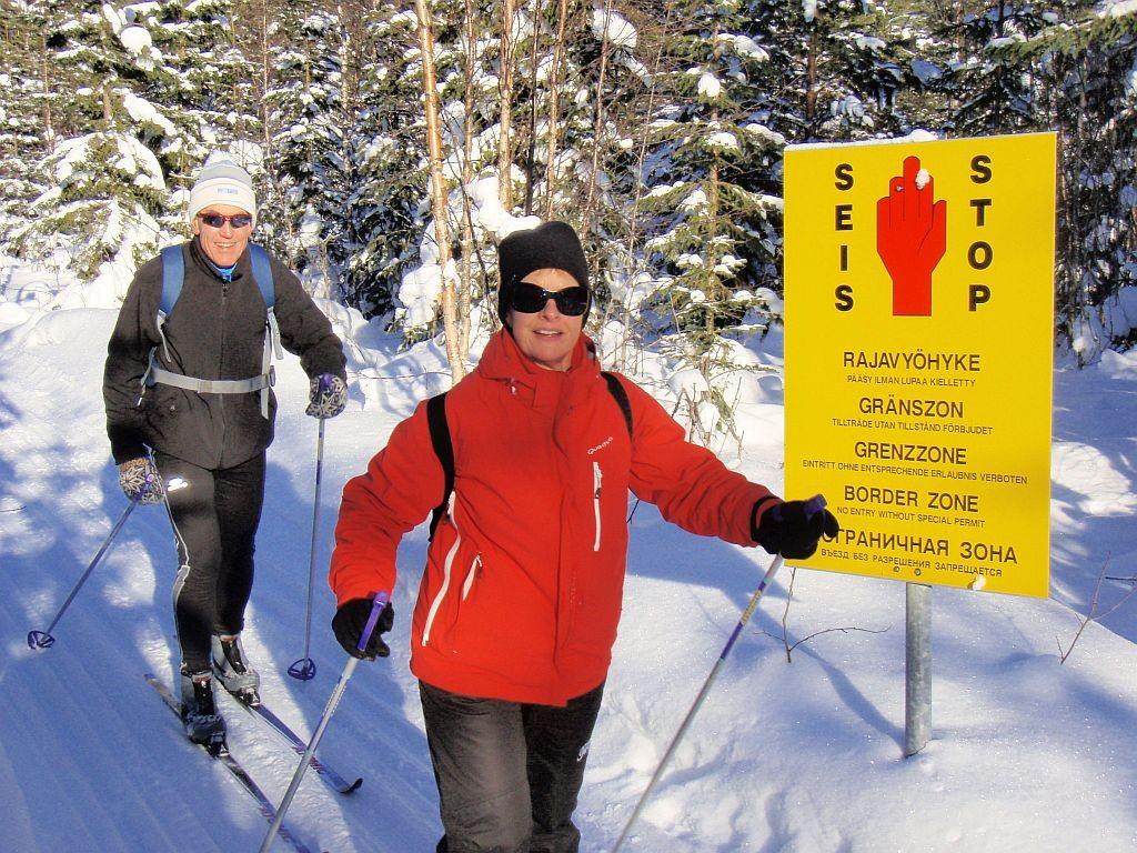 Iloiset hiihtäjät itärajalla rajavyöhyke-kyltin edessä.