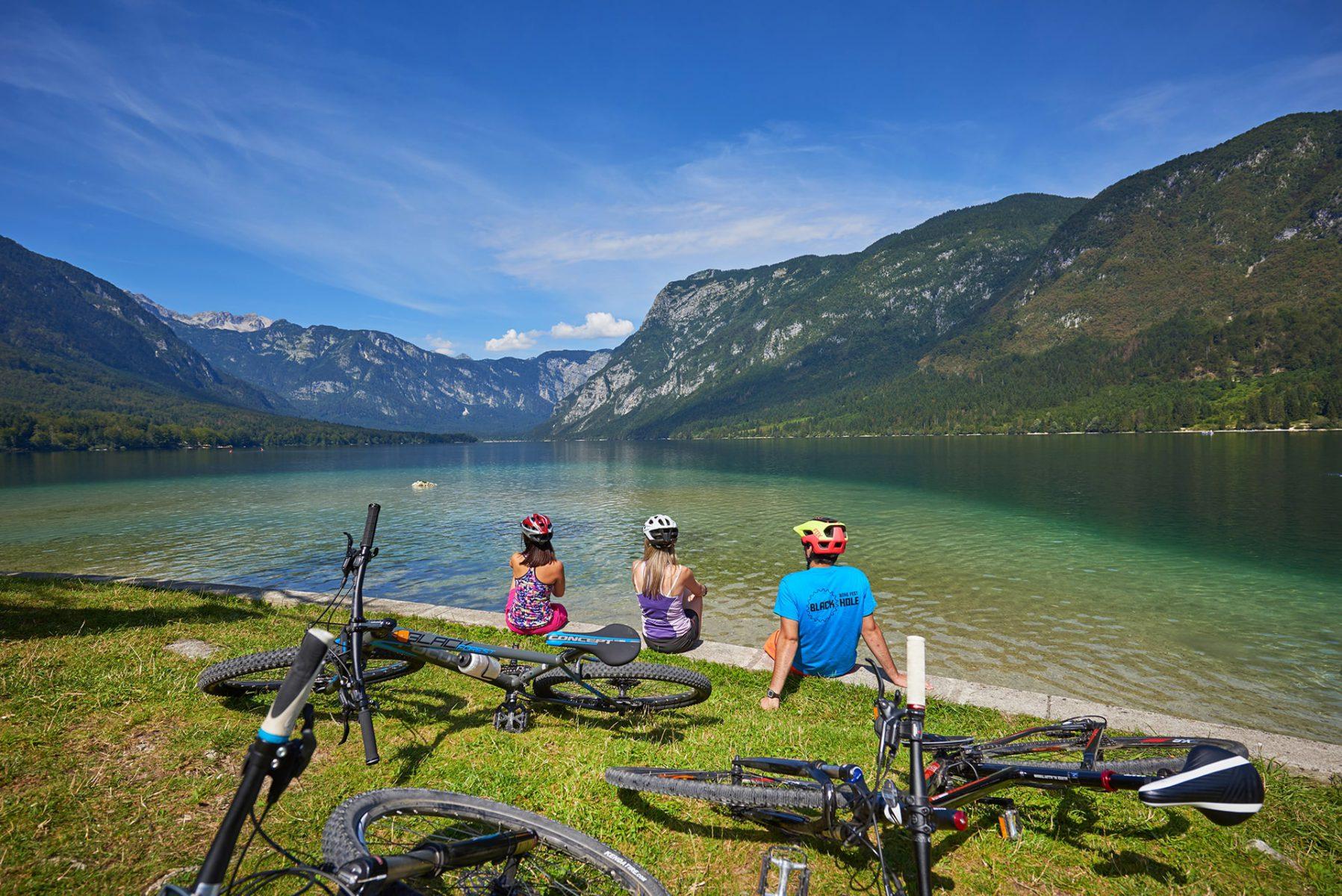 Pyöräilijöitä istuskelemassa Bohinj-järven rannalla Sloveniassa.