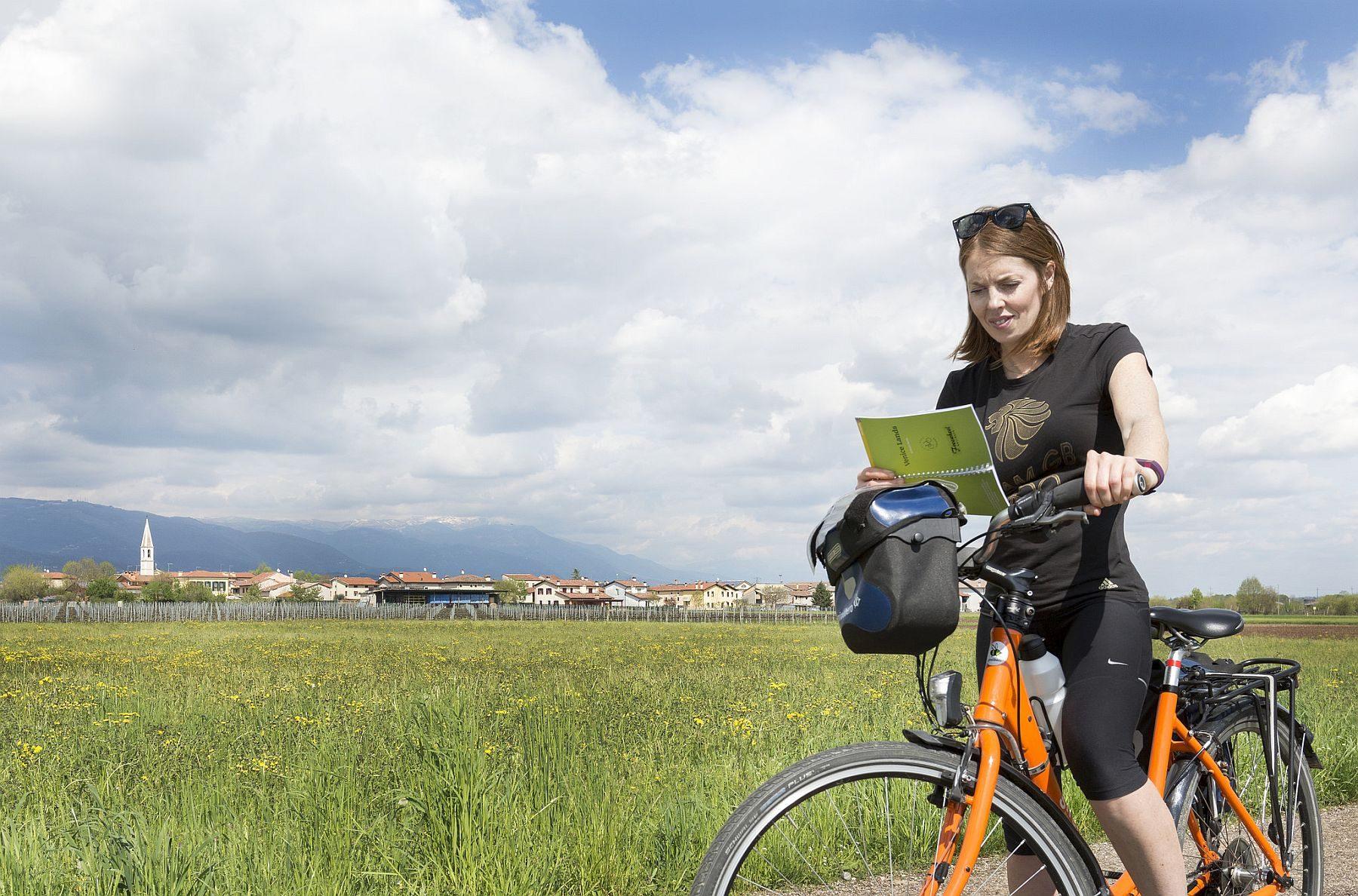 Nainen on pysäyttänyt pyörän tien laitaan ja lukee karttaa.