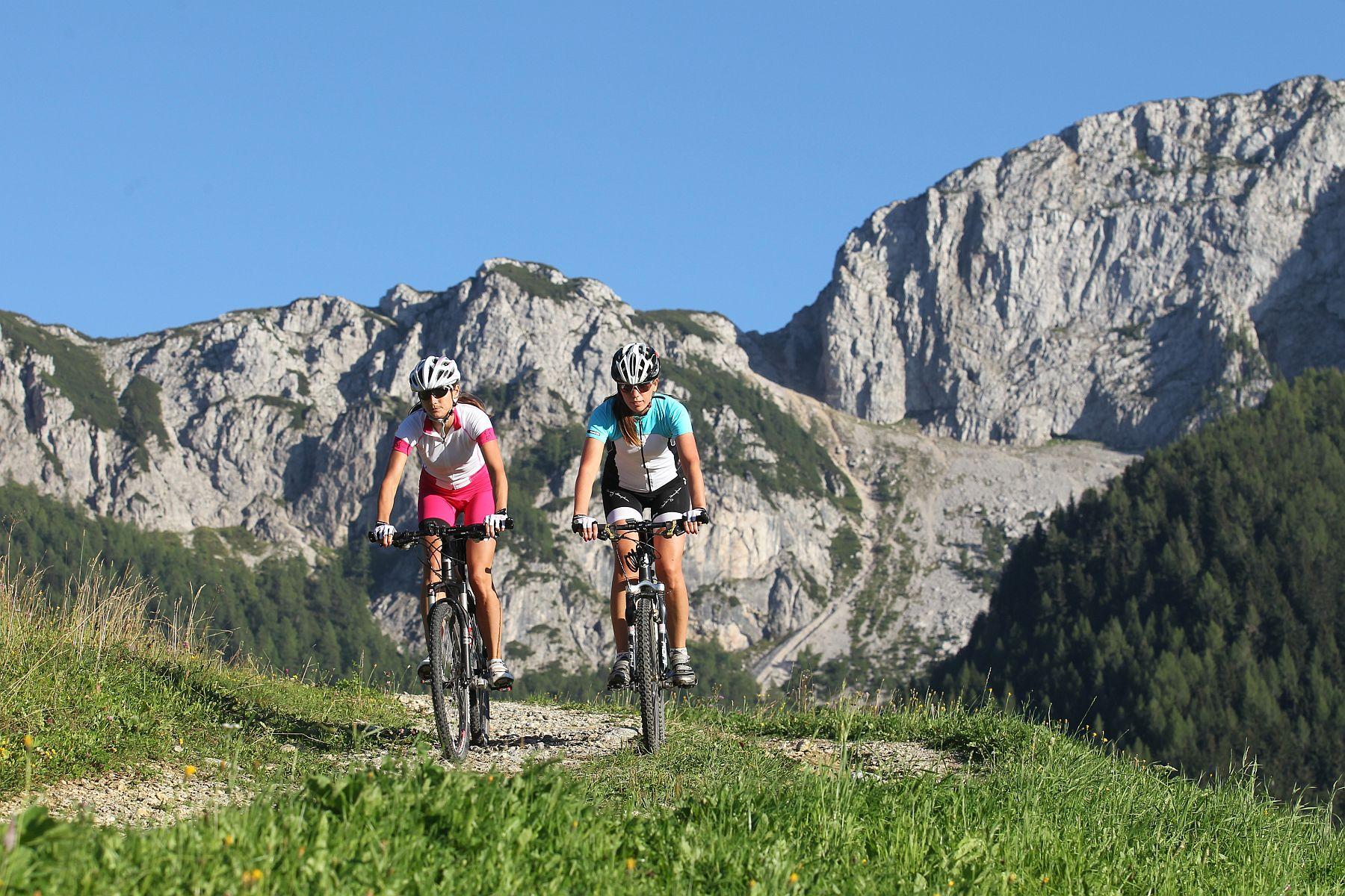 Maastopyöräilijät vuoristomaisemassa.
