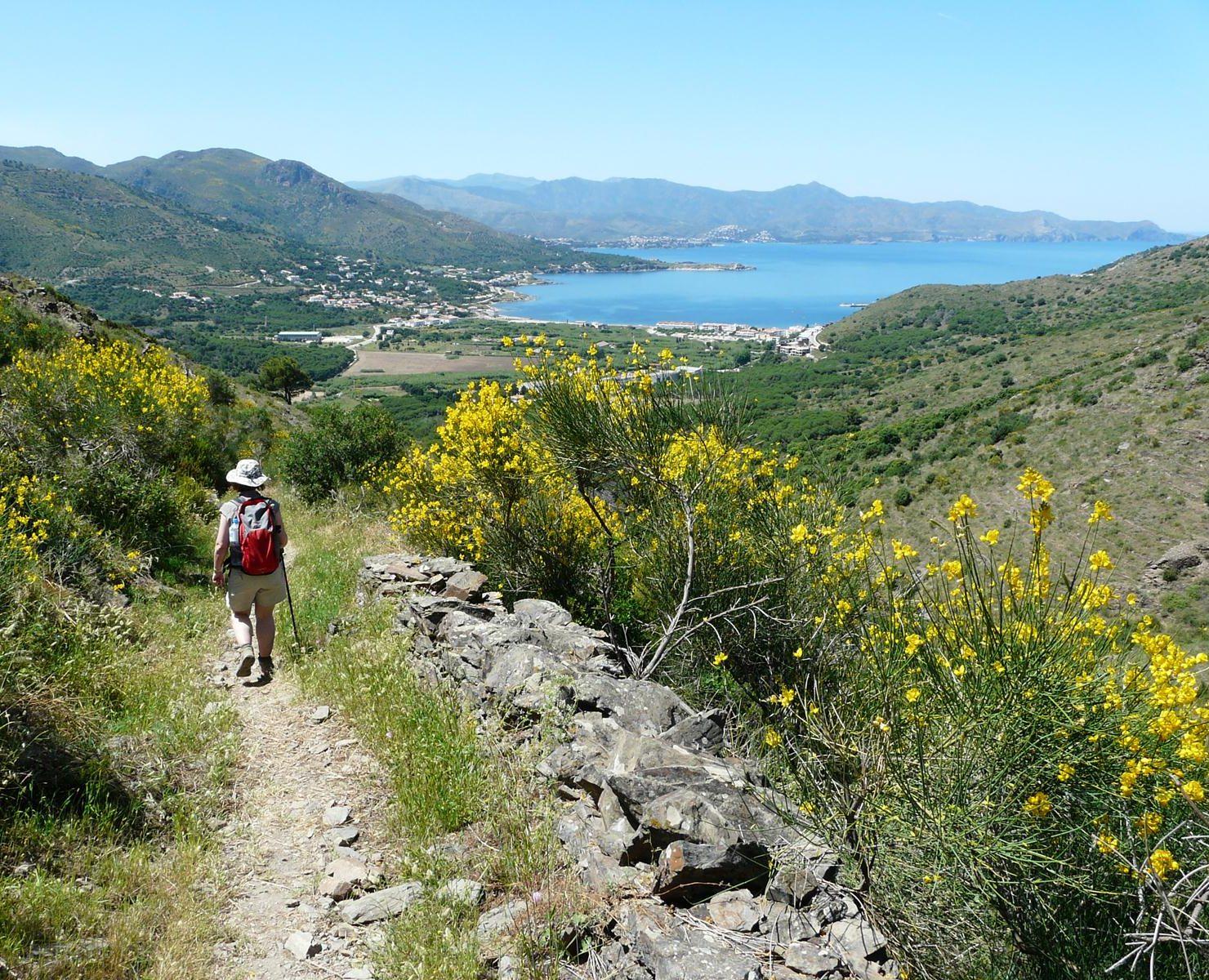 Vaeltaja lähestyy Cadaquesia alamäkeen viettävällä polulla.