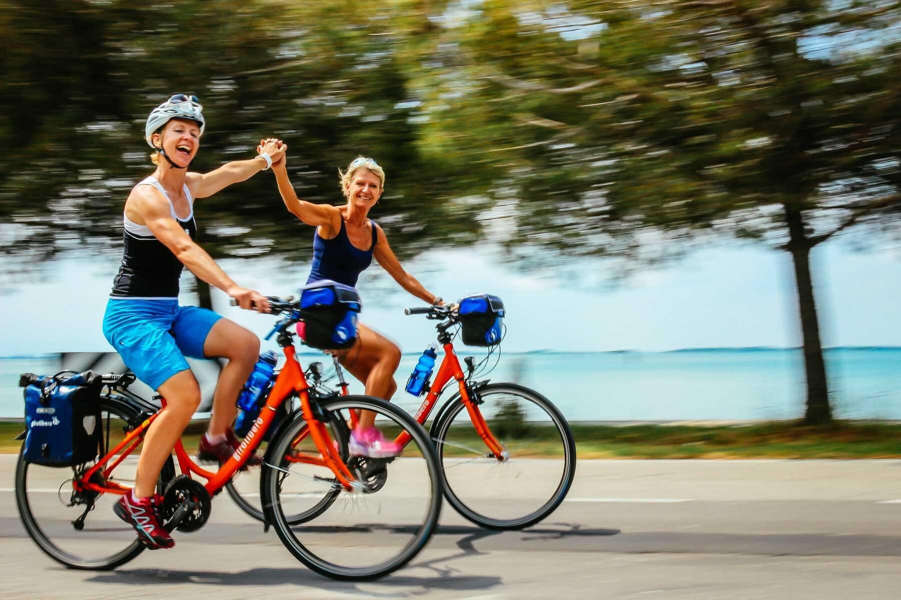 Naiset oransseilla pyörillään ajavat iloisesti vilkuttaen