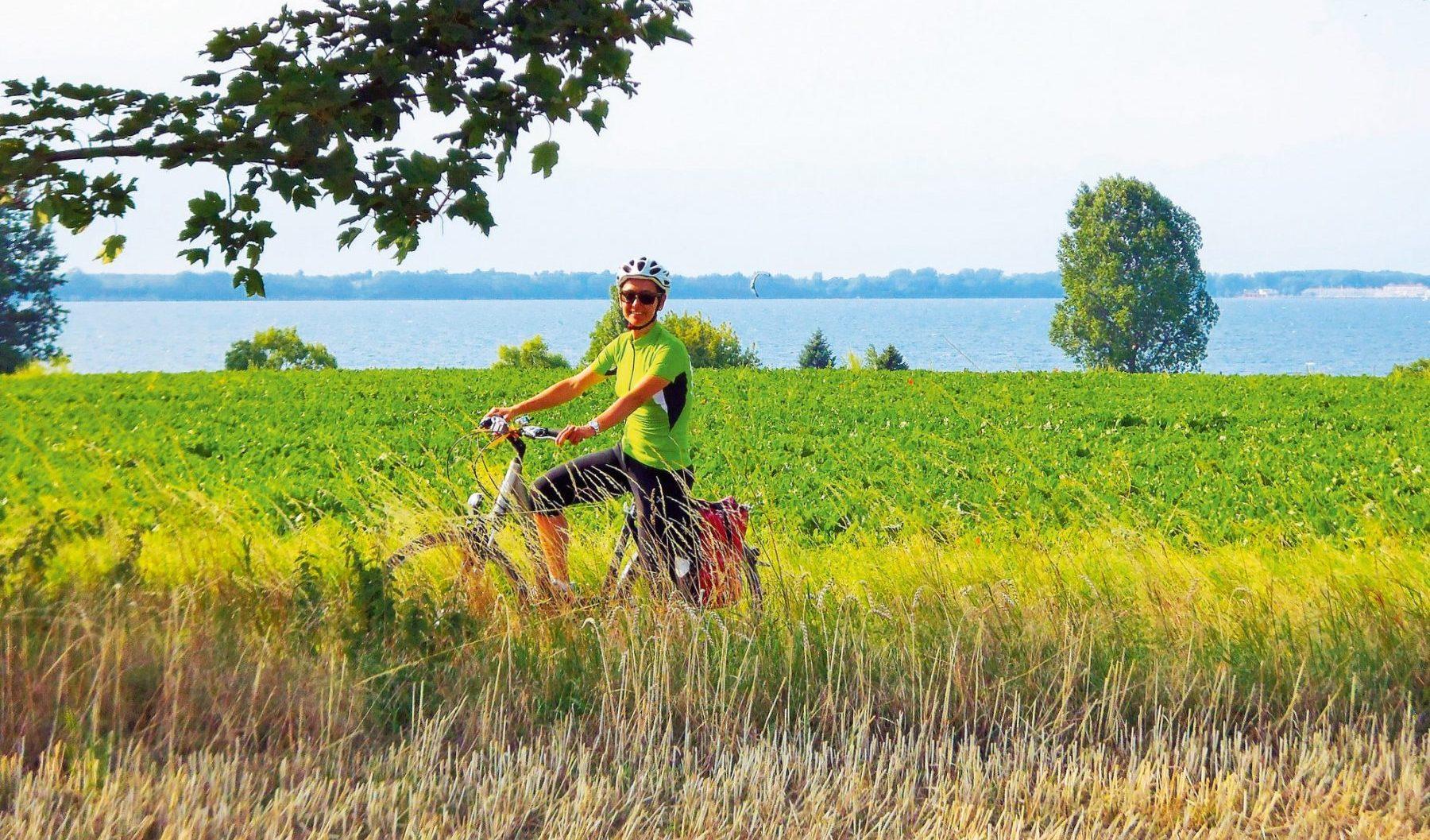 Iloinen nainen pyöräilee pellon laitaa. Taustalla kimmeltää järvi.