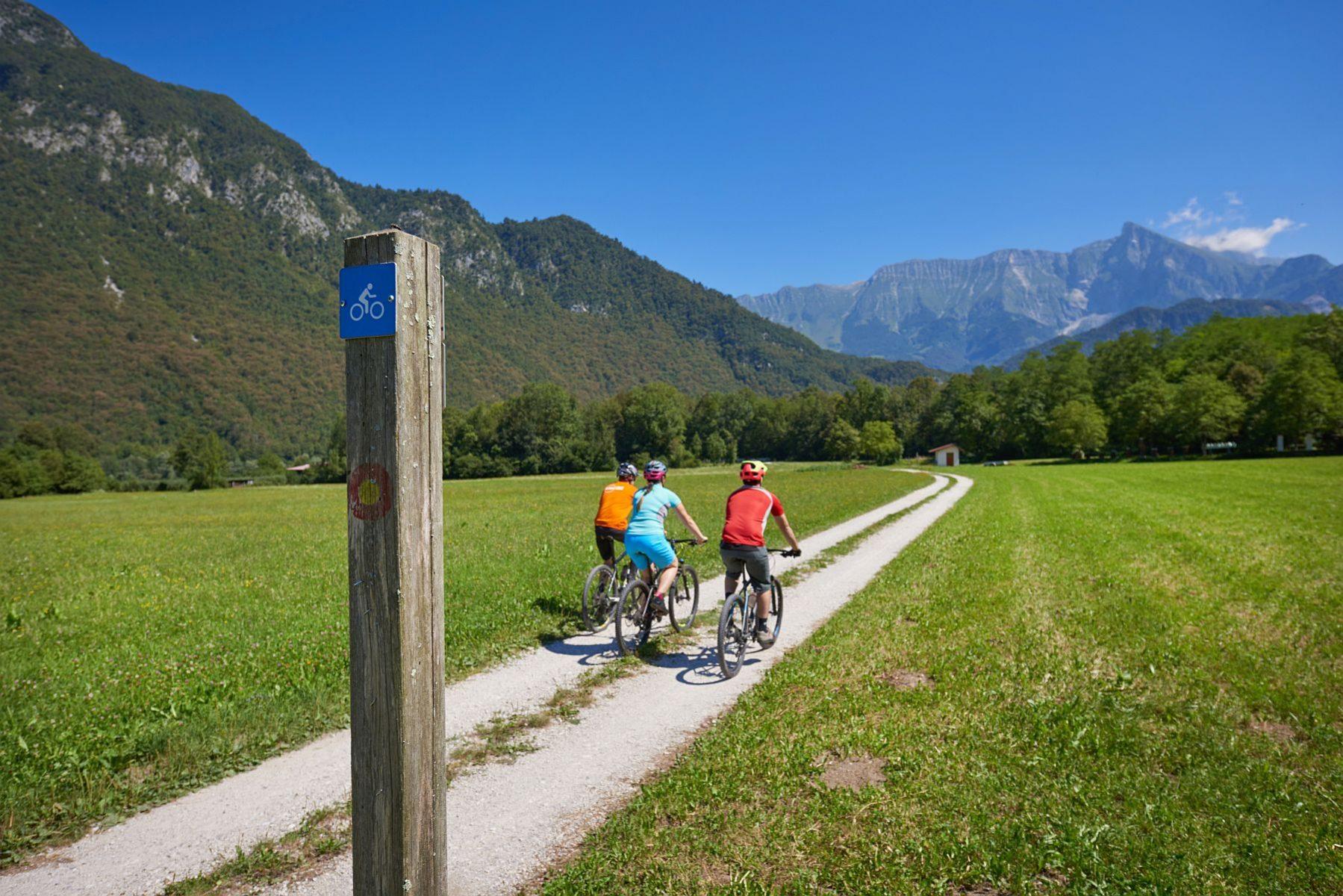 Pyöräilijöitä vuoriston ympäröimällä pienellä hiekkatiellä.
