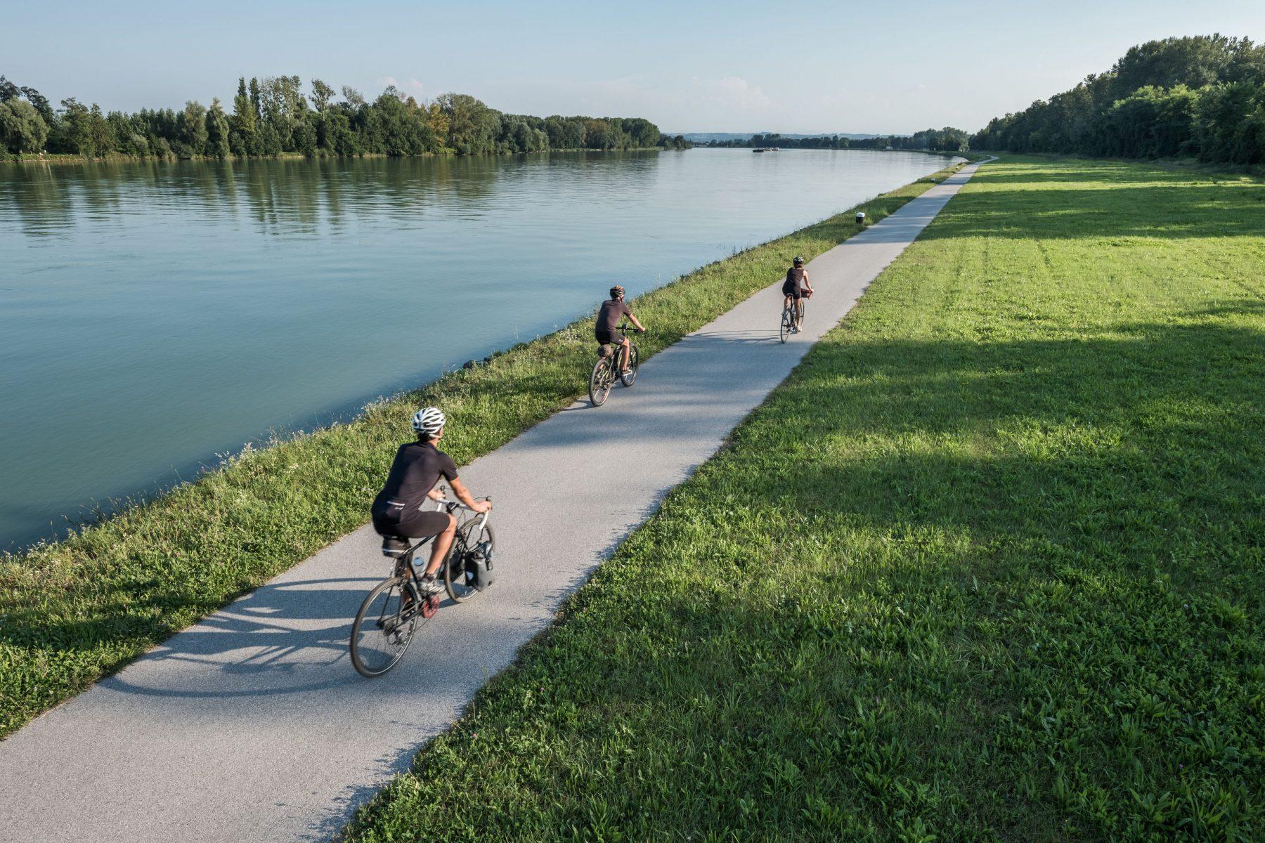Pyöräilijöitä Tonavan pyörätiellä aivan veden äärellä.