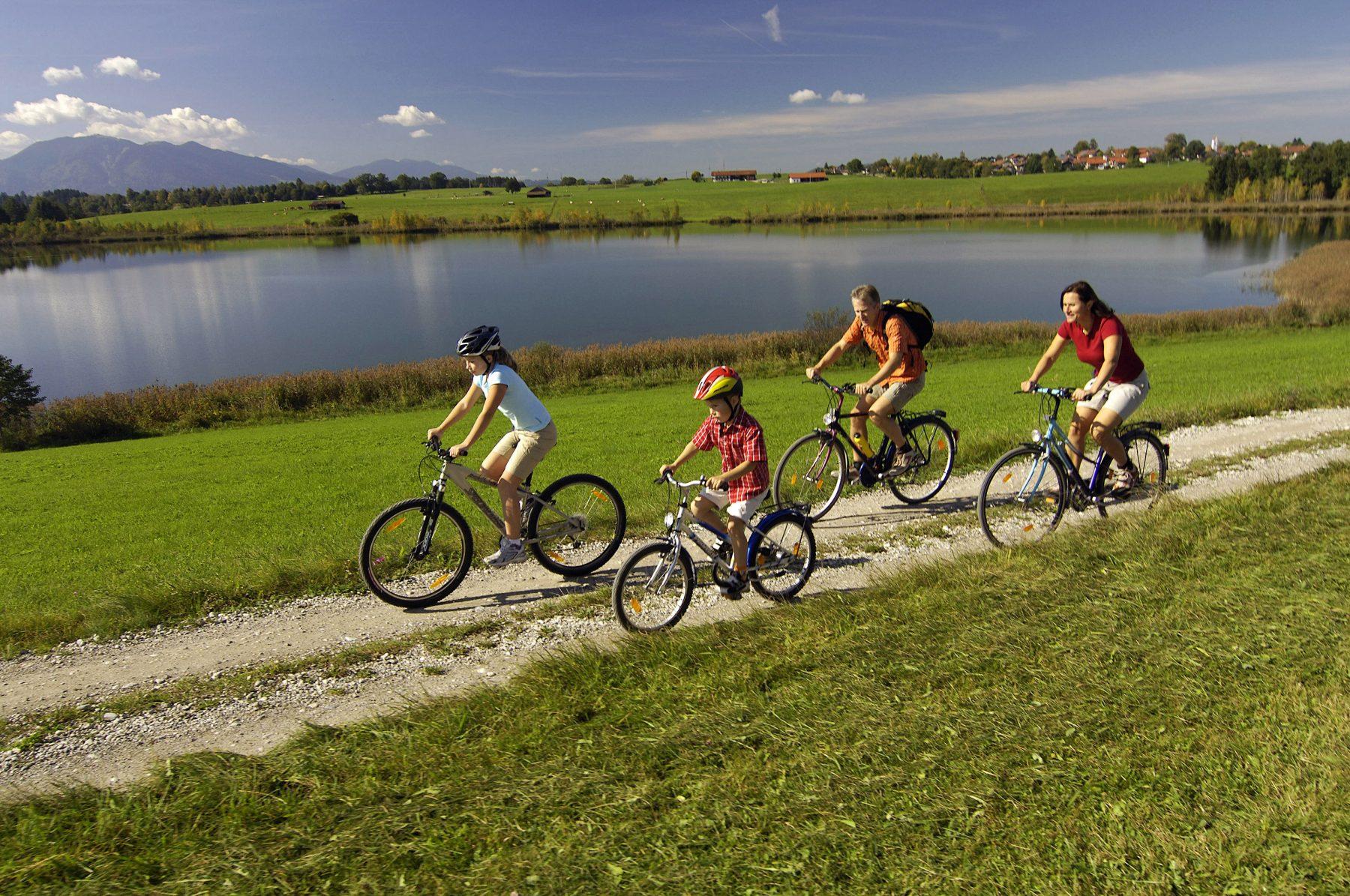 Perhe pyöräilee pyörätietä järven rannalla.