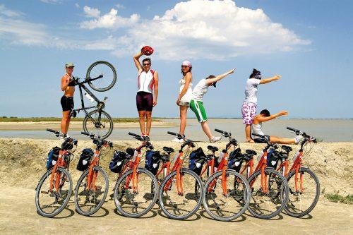 Kuusi ihmistä seisoo tai istuu polkupyörien päällä muodostaen käsillään ja jaloillaan sanan bike.